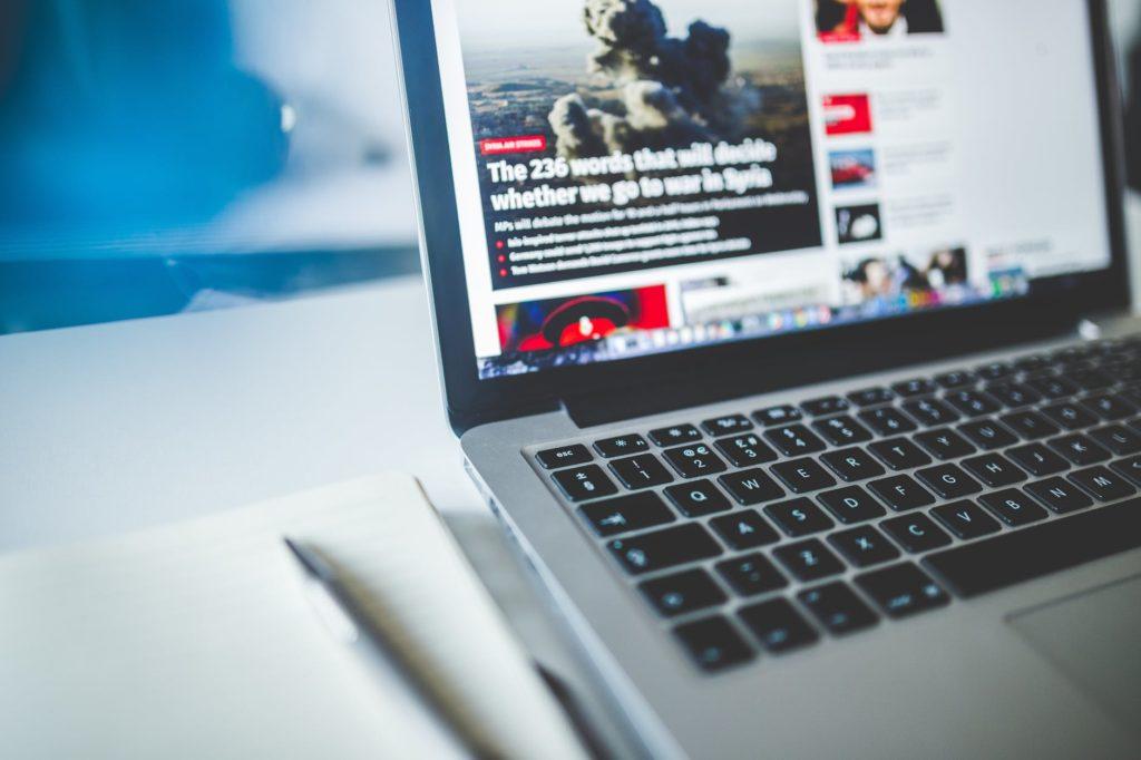 gray laptop computer near journals